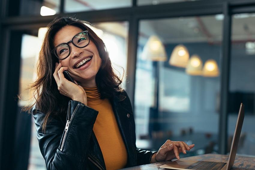 Chica sonriente mientras habla por teléfono y trabaja en su portatil.