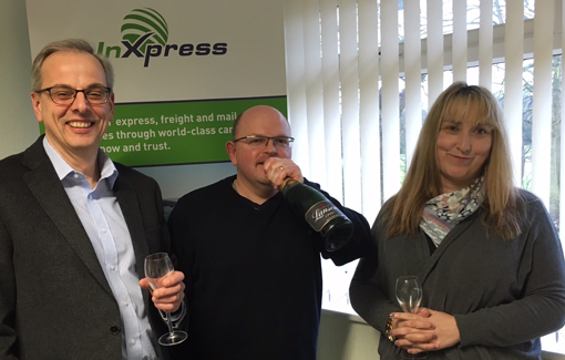 InXpress Franchisee Rob Williams drinking champagne with team