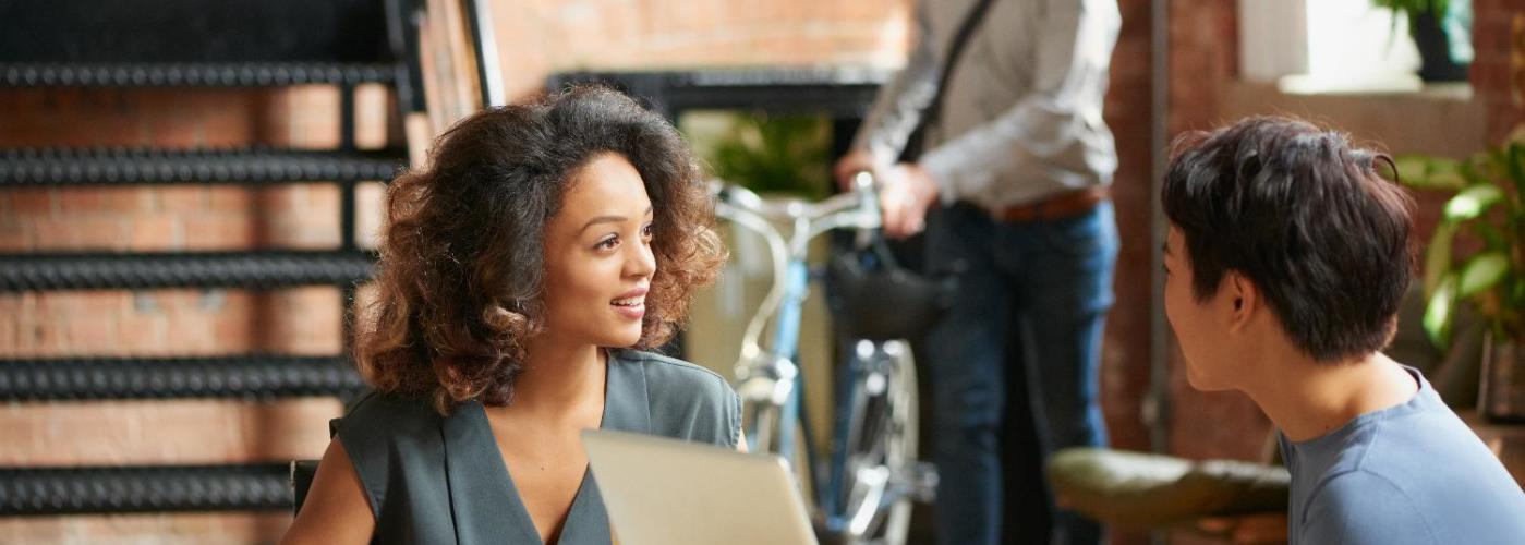 Dos personas hablando animadamente en una reunión de negocios en una cafetería