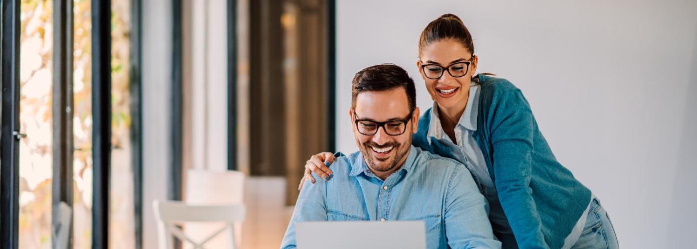 Dos personas sonrientes mirando la pantalla de un ordenador portatil