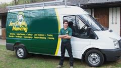 Man in front of Jim's Mowing van